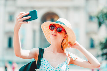 Portrait shot of young female tourist wearing straw hat and sunglasses while taking selfie in the city.