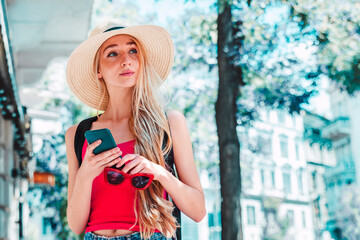 Young woman text messaging while standing on the street