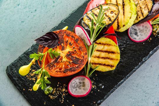 Tasty grilled vegetables on pan on dark background. Healthy food, summer food concept.