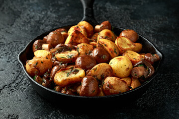 Baked potato with mushrooms and herbs in iron cast pan