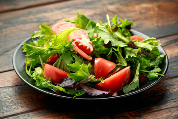 Fresh tomato salad with vegetables on black plate. wooden table. healthy food.