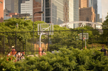 Public basketball court with modern skyscrapers on background