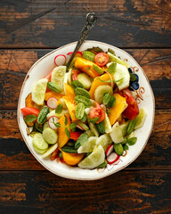 vegetarian vegan salad with crystal lemon cucumbers, cucamelon, radishes and orange tomato. Healthy food concept