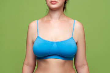 Woman in blue top bra with big natural breasts on green background