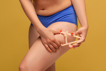 Woman measuring her body fat with caliper on yellow background