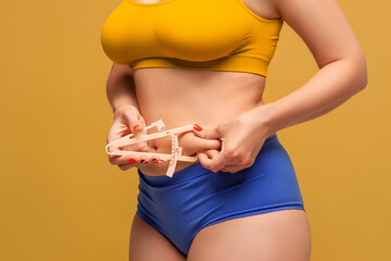 Beauty woman in colorful underwear measuring her body fat with caliper on yellow background
