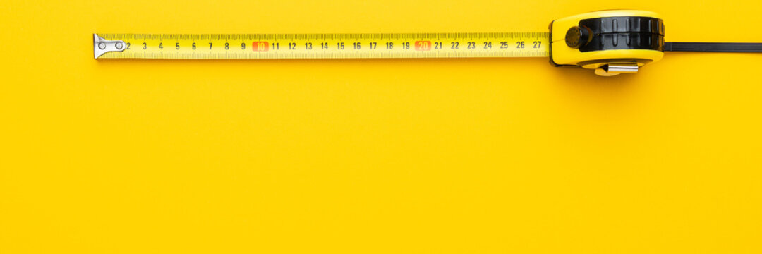 Tape measure on the yellow background with copy space. Panoramic photo of yellow tape measure.