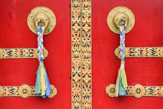 Ornate door handles and prayer scarves on ancient Buddha park monastery at Ravangla in South Sikkim, India. Red color door at Buddha Park of Ravangla. Door handles at Buddha Park Monastery in Sikkim.