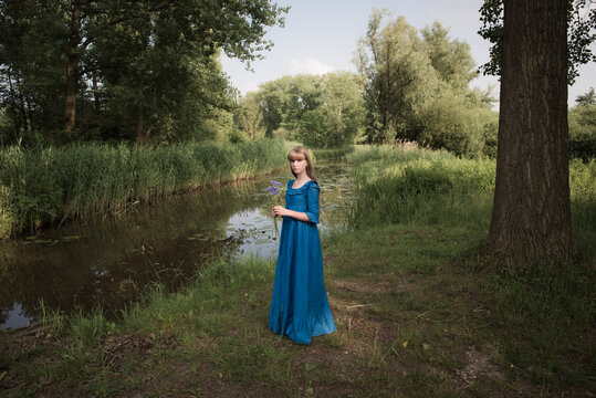 Portrait of teenage girl in blue dress holding flowers while standing by river