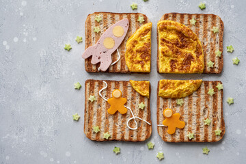 Funny cosmos sandwiches with rocket and astronauts on the omelet moon