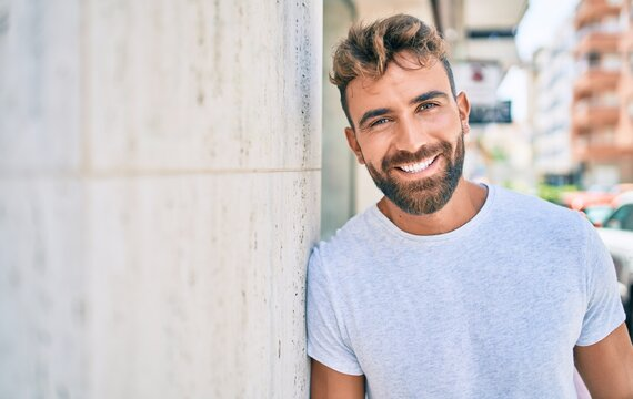Young hispanic man smiling happy leaning on the wall at the city