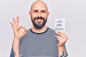 Young handsome man holding we are equal paper doing ok sign with fingers, smiling friendly gesturing excellent symbol