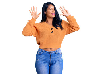 Hispanic woman with long hair wearing casual winter sweater showing and pointing up with fingers number nine while smiling confident and happy.