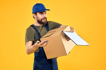 Worker male courier delivering boxes packaging documents yellow background