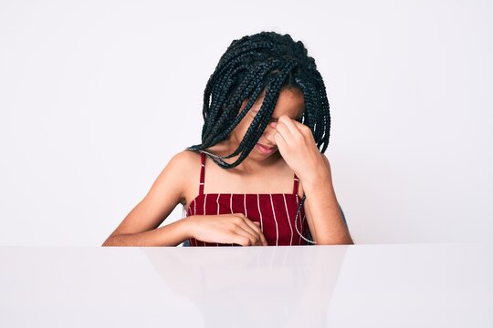 Young african american girl child with braids wearing casual clothes sitting on the table tired rubbing nose and eyes feeling fatigue and headache. stress and frustration concept.