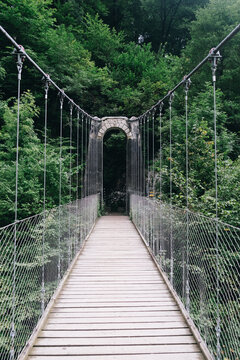Inside view of the Holtzarte suspension bridge with wooden floor and lush forest in the background