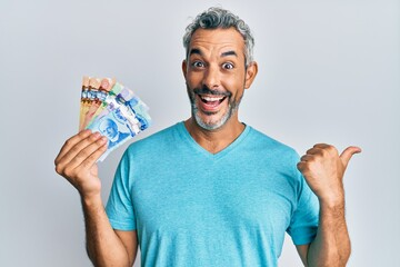 Middle age grey-haired man holding canadian dollars pointing thumb up to the side smiling happy with open mouth