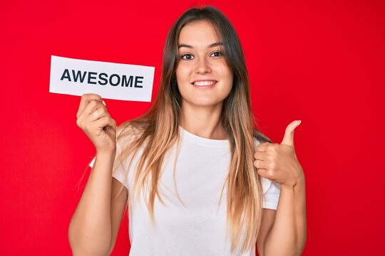Beautiful caucasian woman holding awesome banner smiling happy and positive, thumb up doing excellent and approval sign