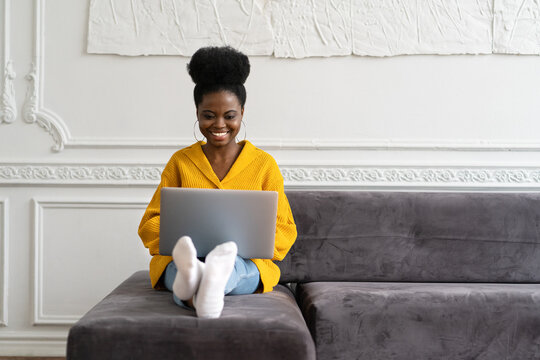 Smiling African American millennial woman with afro hairstyle wear yellow cardigan sitting on sofa, resting, looking at camera webcam and talking on a video call or skype with friends, watching movie