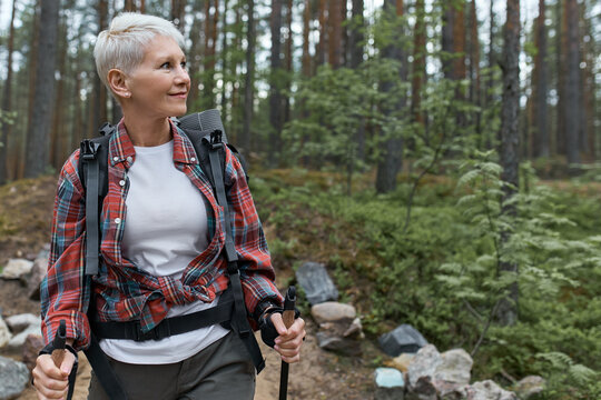 Outddor portrait of happy European female pensioner with backpack and poles, enjoying beautiful nature while nordic walking in pine forest. Aging, people, active lifestyle and health concept