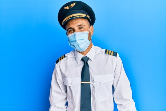 Handsome man with beard wearing airplane pilot uniform wearing safety mask looking positive and happy standing and smiling with a confident smile showing teeth