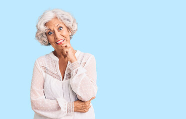 Senior grey-haired woman wearing casual clothes looking confident at the camera with smile with crossed arms and hand raised on chin. thinking positive.