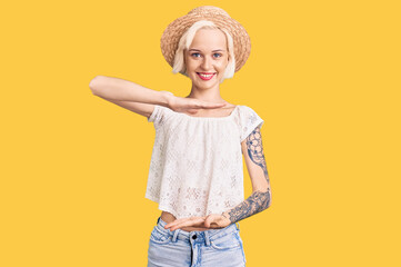 Young blonde woman with tattoo wearing summer hat gesturing with hands showing big and large size sign, measure symbol. smiling looking at the camera. measuring concept. Papier Peint