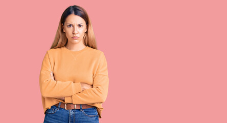 Beautiful young woman wearing casual clothes skeptic and nervous, disapproving expression on face with crossed arms. negative person.