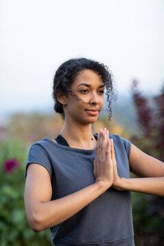 Black woman practicing yoga outdoors in garden