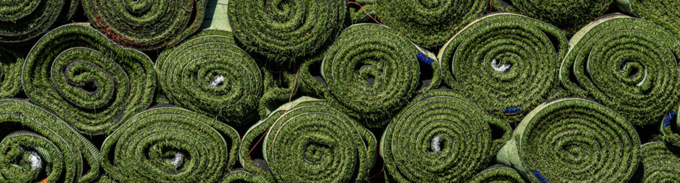 Green rolls of new artificial turf ready for installation on an outdoor sports field