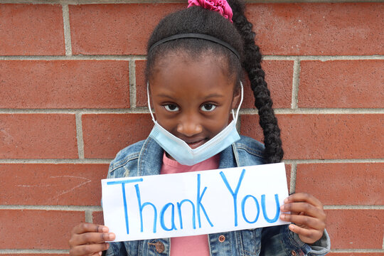 Black Kid outside holding Thank You Sign with mask on