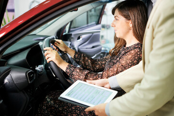 Close-up of manager of car salon standing with tablet pc and suggesting to female customer to insure her new car