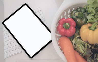 Top view of blank screen tablet with basket of vegetable on counter table in kitchenroom.