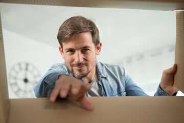 portrait of a man looking for something inside box