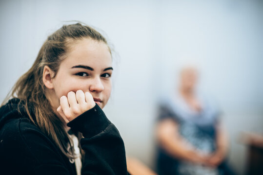 Portrait of a young girl in the classroom and the teacher in the background blurred.