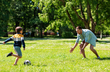 Photo sur Plexiglas Pain family, fatherhood and people concept - happy father and little son with ball playing soccer at summer park