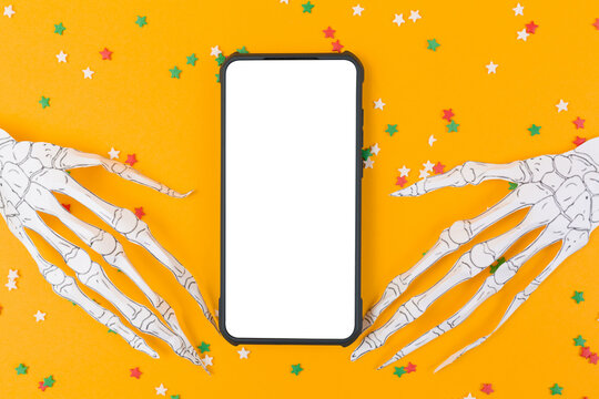 Smartphone is surrounded by skeleton hands made of paper. Orange background with decorative stars. Flat lay. Mock up. The concept of Halloween and technologies
