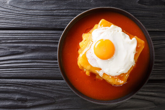 Hot Francesinha sandwich with sausages and meat, melted cheese, poured with tomato beer sauce and topped with a fried egg close-up in a plate on the table. horizontal top view from above