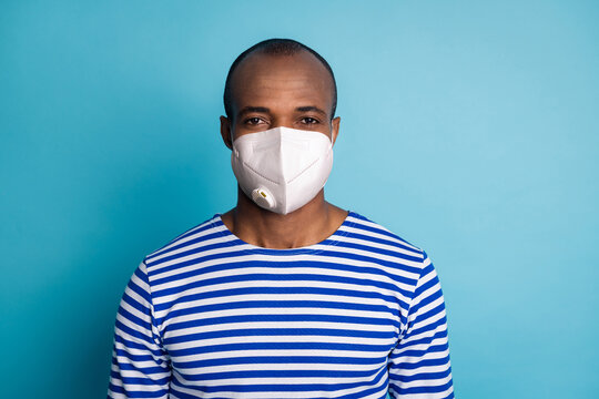 Portrait of charismatic dark skin guy travel trip on covid infection quarantine stay safe look in camera wear striped sailor vest white medical mask isolated over blue color background