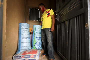 A farmer inspects what is left of his chicken feed inside the feed storage at his poultry farm in Kubwa Abuja