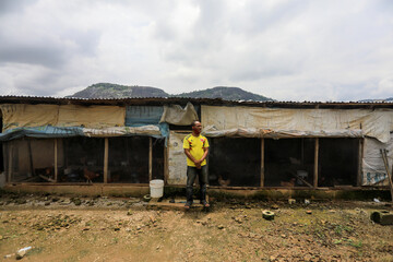 A farmer stands in front of his poultry farm in Kubwa Abuja