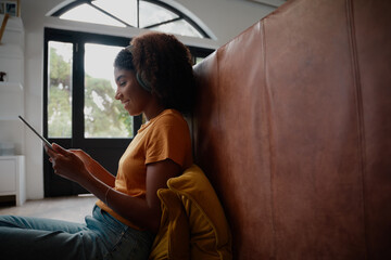 Side view of young african woman sitting on floor using digital tablet with headphones while on...