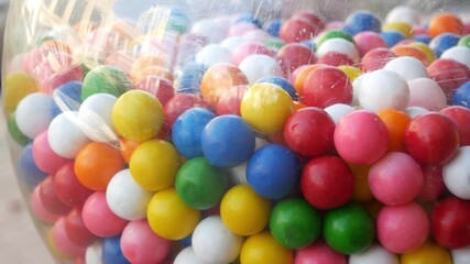 Colorful gumballs in classic vending machine, USA. Multi colored buble gums, coin operated retro dispenser. Chewing gum candies as symbol of childhood and summertime. Mixed sweets in vintage automate