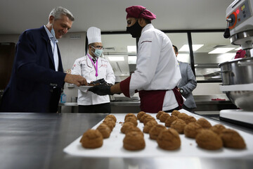 The United Nations High Commissioner for Refugees (UNHCR) Filippo Grandi prepares to taste some food during his visit to Luminus Technical University College in Amman