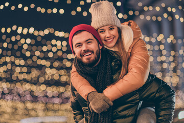Photo of holly guy hug piggyback his girlfriend under outside evening x-mas illumination wear season outerwear