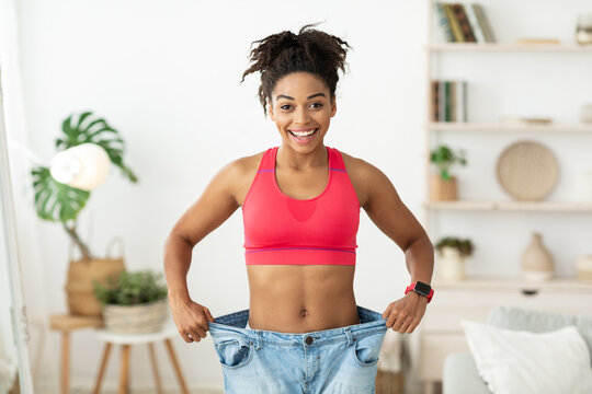 African Woman After Slimming Showing Old Oversize Pants Standing Indoors