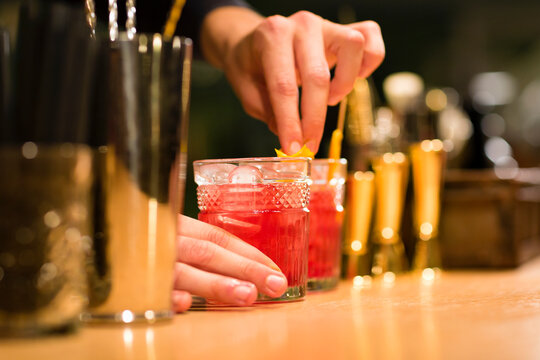 Crop barman decorating cocktail glass with orange