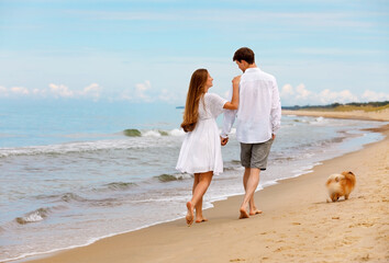 Sweet couple of young lovers with a dog walk along the beach