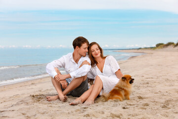 Nice couple of young lovers with a dog relax on the beach
