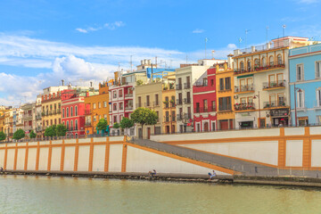 Seville, Andalusia, Spain - April 19, 2016: sunset view of famous colorful houses of Triana neighborhood on west bank of the Guadalquivir River. Seville city sightseeing from touristic Cruise.